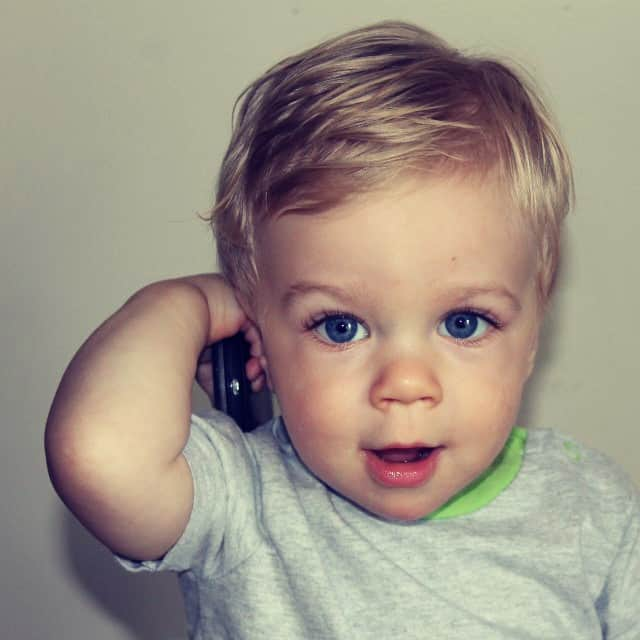 Sweet baby, playing and talking on a remote control.